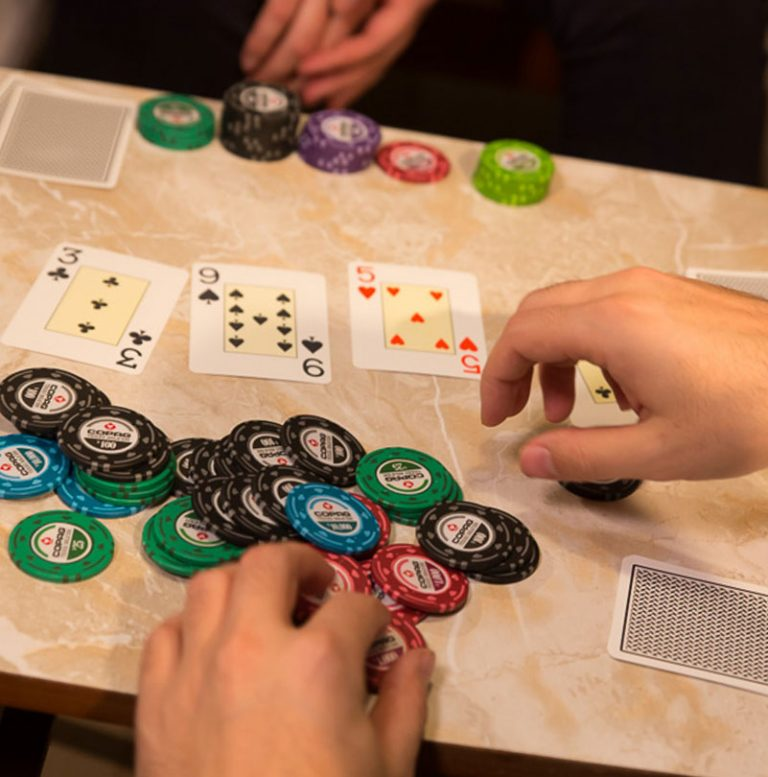 Close up of people playing with Copag Poker chips and Copag plastic Playing Cards