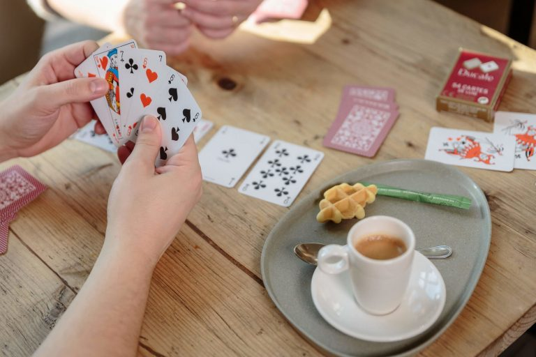 Two people enjoying a coffee and playing a card game with Ducale Playing Cards