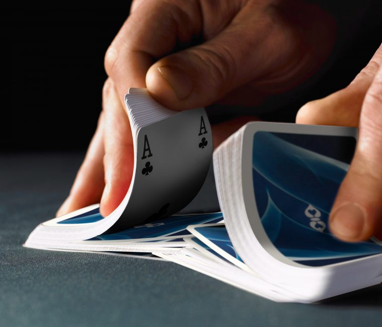 Man shuffling Ace playing cards, close-up