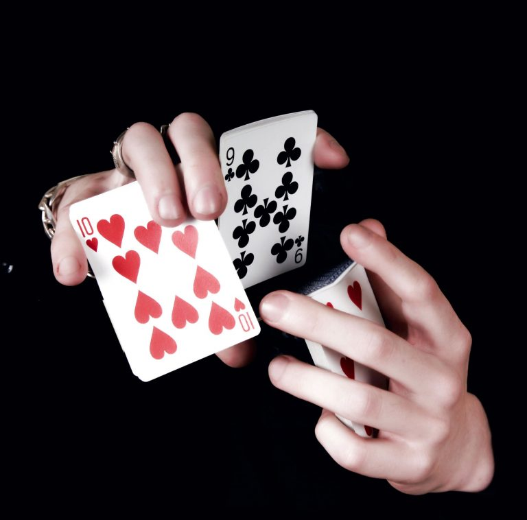 Close up of hands doing a card trick with Cartamagic cards