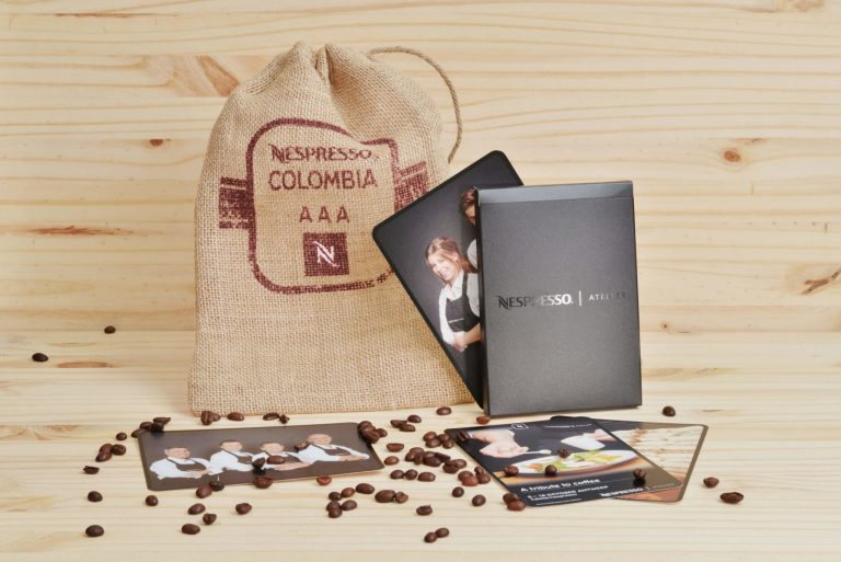Coffee Bean bag with deck of cards of l'Atelier Nespresso on a wooden table with loose coffee beans