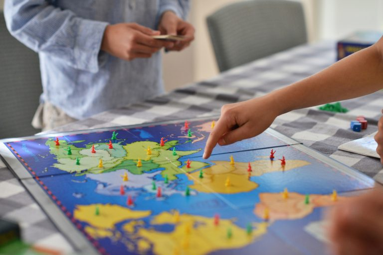 Person pointing to map on Risk board game