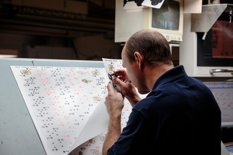 Man checking quality of a playing cards printing sheet